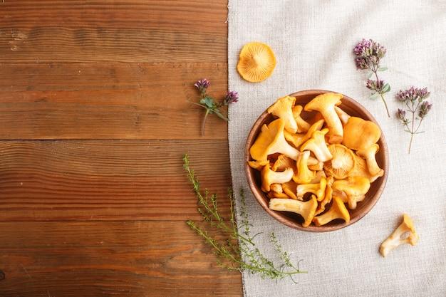 Champignons girolles dans un bol en bois et herbes aromatiques avec textile en lin. vue de dessus. Photo Premium