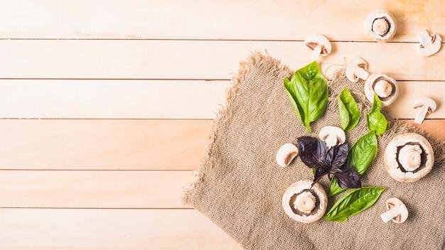 Champignons avec légume-feuilles sur sac de jute sur la planche de bois Photo gratuit