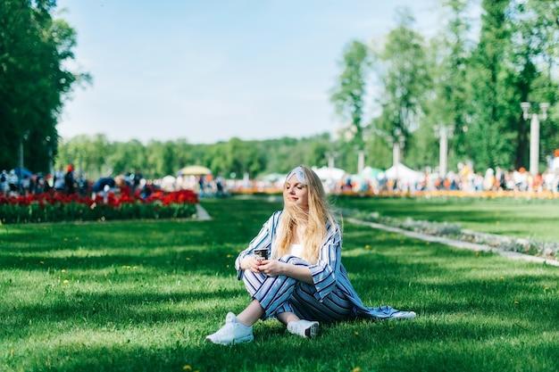 Chanceuse Jolie Femme Est Assise Sur L'herbe Verte En Pyjama Et Masque De Sommeil Et Profite Du Soleil Et De Boire Du Café Photo Premium