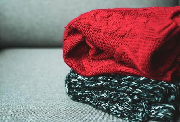 Chandails chauds sur un canapé gris Photo Premium
