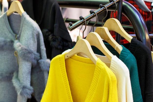 Chandails tricotés en laine à la mode jaune ceylan et autres couleurs suspendus à des cintres dans le magasin, gros plan Photo Premium