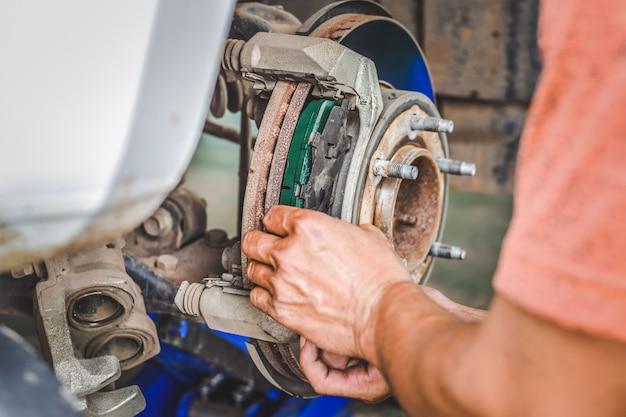 Changement des plaquettes de frein et vérification du système de freinage dans la voiture du garage Photo Premium