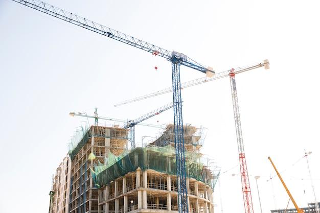 Chantier de construction comprenant plusieurs grues travaillant sur un complexe de bâtiments Photo gratuit