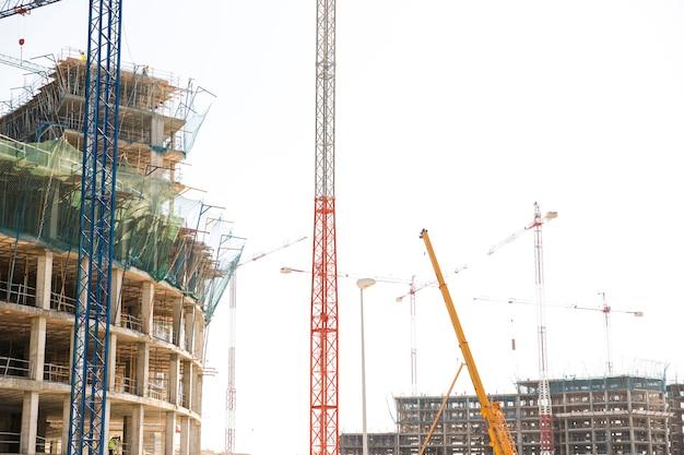 Chantier de construction avec grues et bâtiments incomplets Photo gratuit
