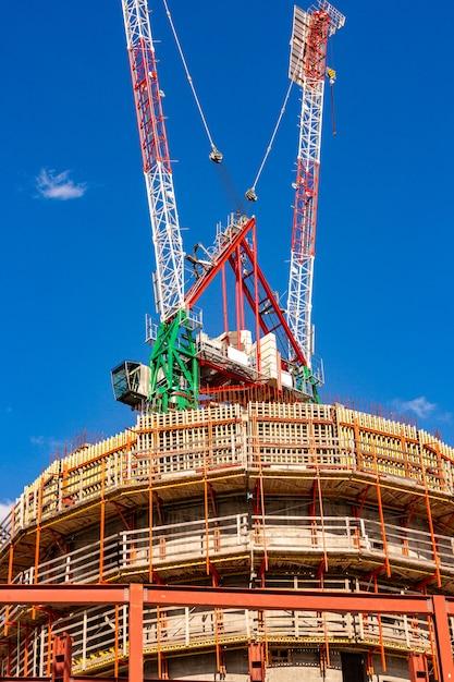 Chantier de construction avec des grues avec un ciel bleu Photo Premium