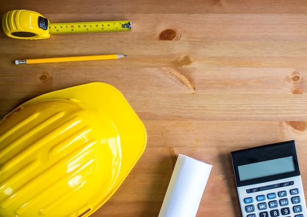 Chapeau de créateur, crayon, ruban à mesurer, plan directeur, calculatrice, plateau de table en bois, vue de dessus, espace de copie Photo Premium