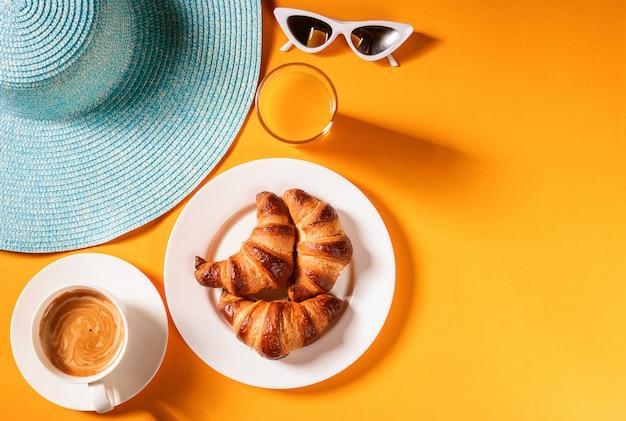 Chapeau, Croissant De Lunettes De Soleil Avec Une Tasse De Café Et Un Verre De Jus D'orange Sur Une Table Jaune Au Soleil Photo Premium