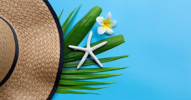 Chapeau D'été Avec étoile De Mer Et Plumeria Ou Fleur De Frangipanier Sur Des Feuilles De Palmier Tropical Sur Fond Bleu. Profitez Du Concept De Vacances D'été. Photo Premium