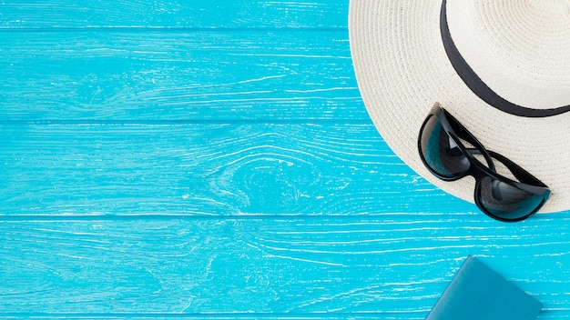 Chapeau d'été et lunettes de soleil près de cahier à bord Photo gratuit