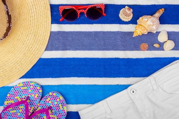 Chapeau de femme paille plage lunettes de soleil vue de dessus shorts seashell tongs fond Photo Premium