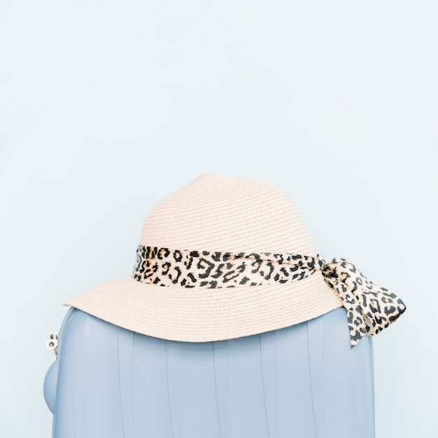 Chapeau de femme sur un sac de voyage en plastique sur fond bleu Photo gratuit