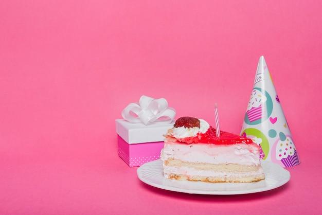 Chapeau de fête; boîte-cadeau et tranche de gâteau avec une bougie sur fond rose Photo gratuit