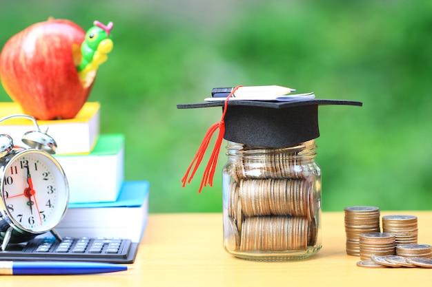 Chapeau de graduation sur la bouteille en verre et des livres Photo Premium