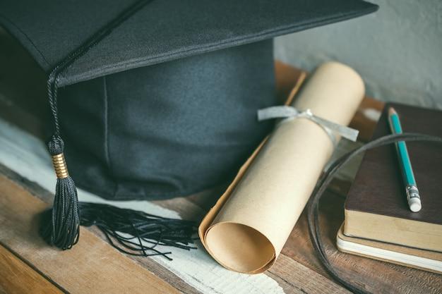 Chapeau de graduation, chapeau avec degré papier sur le concept de graduation de table en bois. Photo Premium