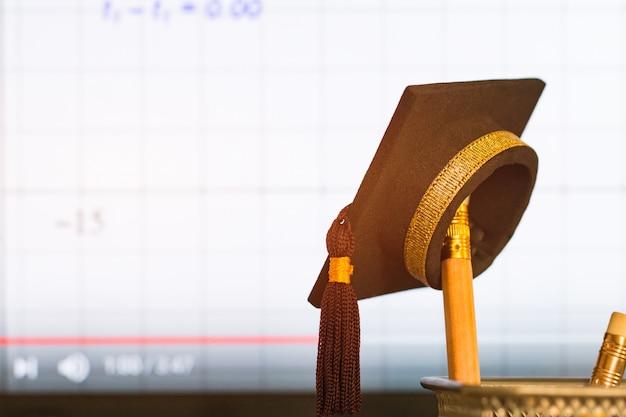 Chapeau de graduation sur les crayons avec le graphique d'équation arithmétique de formule Photo Premium