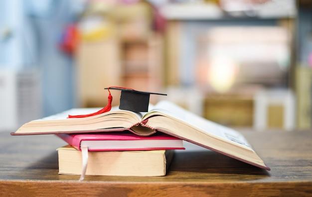 Chapeau de graduation sur un livre sur la table en bois Photo Premium