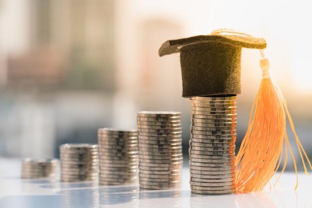 Chapeau de graduation sur la pile de pièces supérieure. Photo Premium