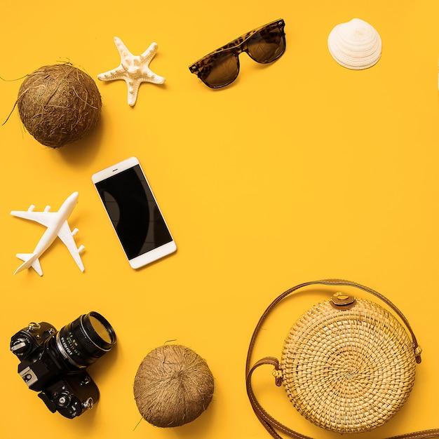 Chapeau de paille, appareil photo argentique rétro, sac en bambou, lunettes de soleil, noix de coco, ananas, coquillages et étoile de mer, avion Photo Premium