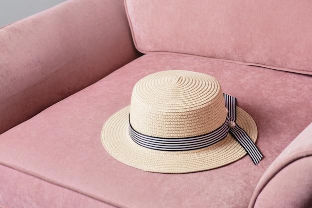 Chapeau de paille sur chaise rose Photo Premium