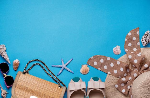 Chapeau De Paille, Lunettes De Soleil Et Chaussures Sur Fond Bleu Photo Premium