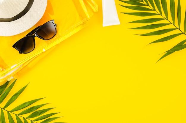 Chapeau De Paille Avec Des Lunettes De Soleil Et Des Feuilles De Palmier Photo gratuit