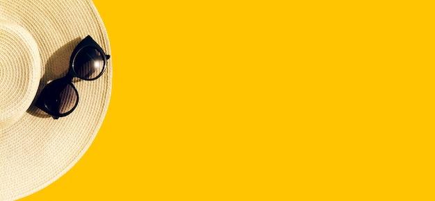 Chapeau de paille avec des lunettes de soleil sur jaune Photo gratuit