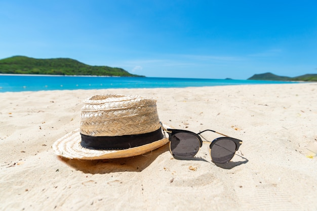 Chapeau de paille et lunettes de soleil sur la mer Photo Premium