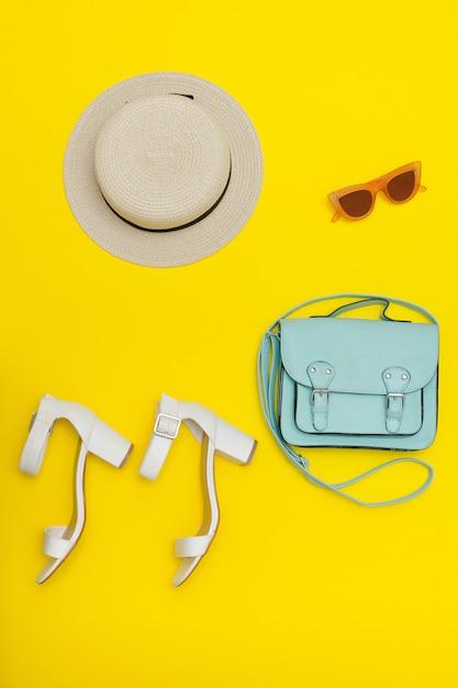 Chapeau de plage pour femme, sac à main, chaussures blanches. fond jaune Photo Premium