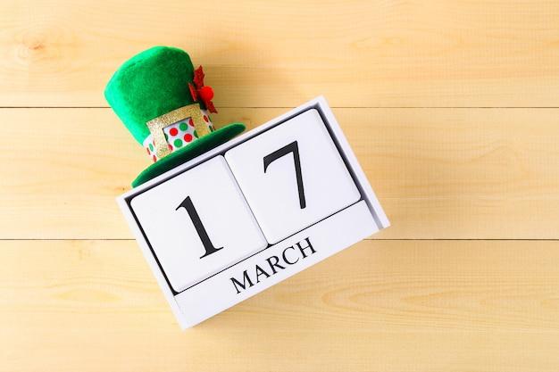 Un chapeau vert sur une table en bois. saint patrick. un calendrier en bois montrant le 17 mars. Photo Premium