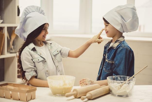 Les Chapeaux De Chef Sourient En Cuisinant Dans La Cuisine. Photo Premium