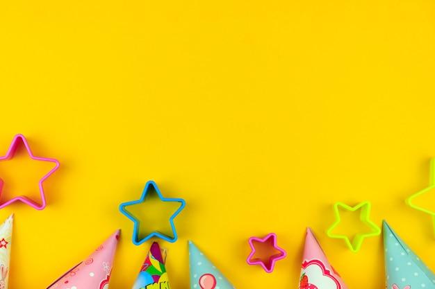 Chapeaux de fête d'anniversaire, ballon et étoiles sur fond jaune avec fond Photo Premium