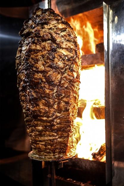 Charbon de shawarma. gros plan de viande de poulet recueillie sur une brochette verticale et grillée au charbon. Photo Premium
