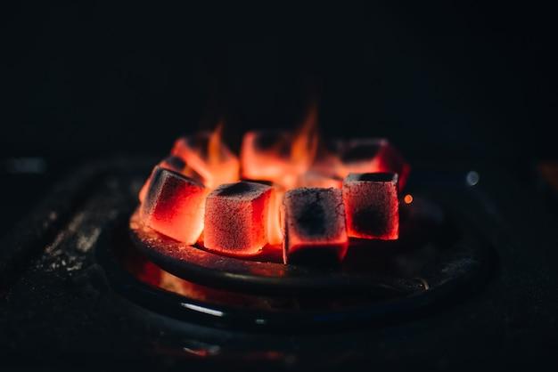 Des charbons ardents pour shisha réchauffés sur le feu dans un bar à narguilé Photo Premium