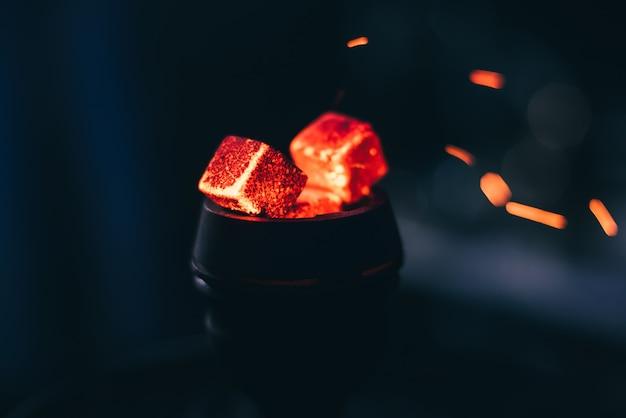 Charbons rouges chauds pour narguilé avec étincelles sur fond sombre Photo Premium
