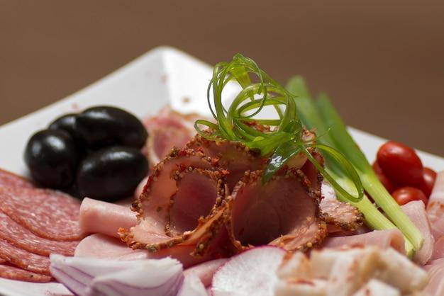 Charcuterie sur plateau - différents types de jambon, bacon, salami, tomates, oignons, feuilles vertes, olives Photo Premium