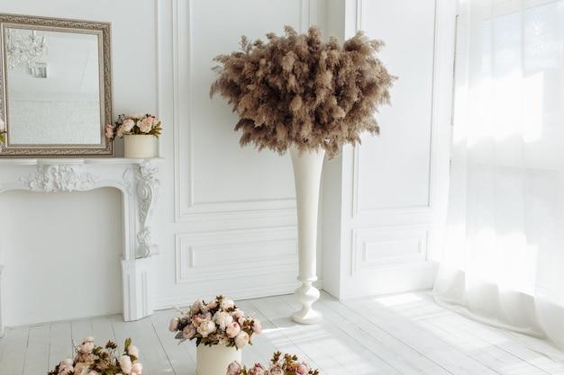 Chardon sec, bardane et roseaux bulrush commun dans un vase isolé sur fond de mur blanc Photo gratuit