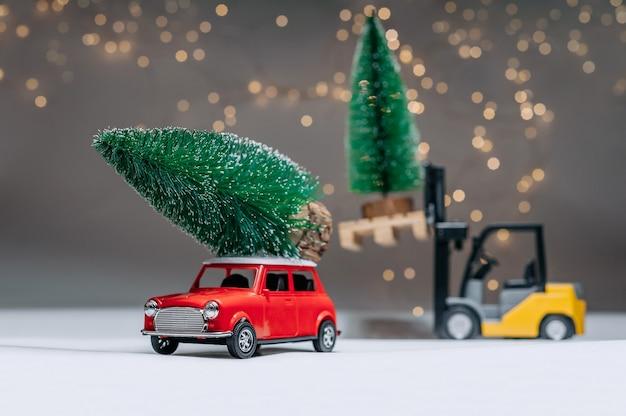 Un Chargeur Et Une Manine Rétro Rouge Portent Des Arbres Verts. Dans Le Contexte Des Lumières Festives. Concept Sur Le Thème De Noël Et Du Nouvel An. Photo Premium