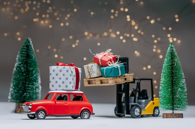 Un Chariot élévateur Charge Des Cadeaux Sur La Voiture Rouge. Dans Le Contexte Des Arbres Verts Et Des Lumières Festives. Concept Sur Le Thème De Noël Et Du Nouvel An. Photo Premium