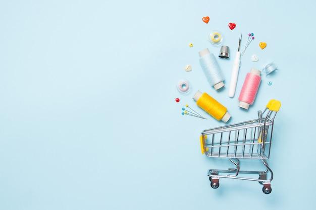 Chariot de supermarché avec accessoires de couture sur fond bleu, couture, broderie. Photo Premium