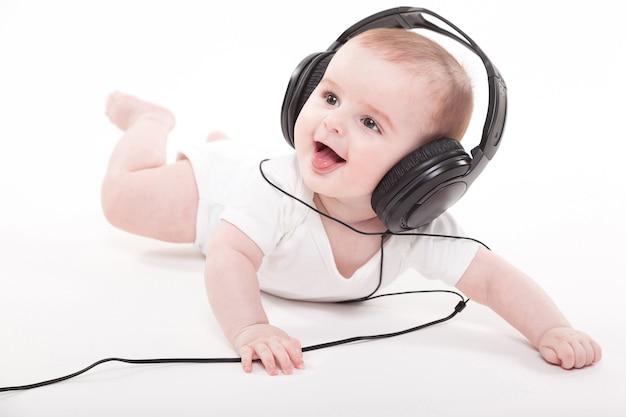 Charmant bébé sur fond blanc avec un casque Photo Premium