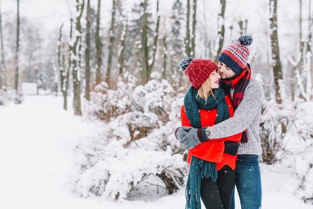 Charmant couple embrassant dans les bois enneigés Photo gratuit