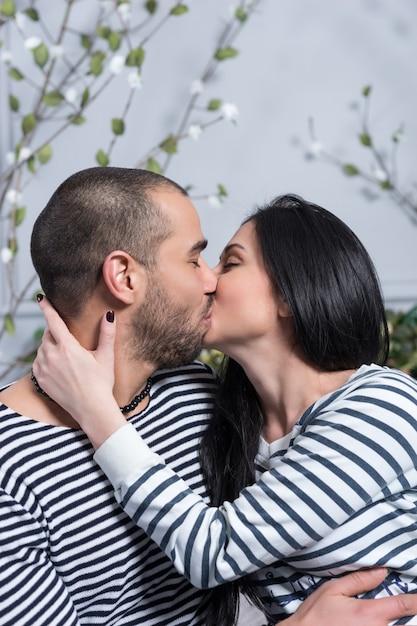 Charmant Couple International En Pulls Rayés S'embrassant Et Se Serrant Dans Ses Bras Assis Sur Le Lit Dans La Chambre Photo Premium
