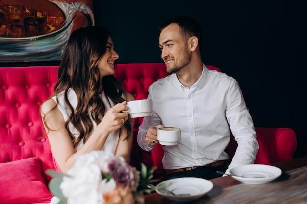 Charmant couple de jeunes mariés boit du café assis sur un canapé rose vif Photo gratuit