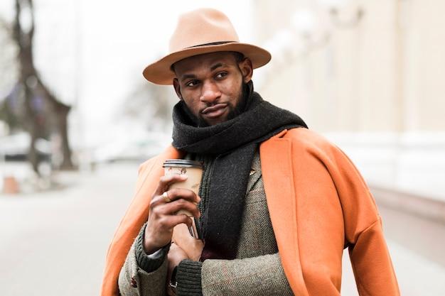 Charmant Homme Posant à L'extérieur Tout En Tenant Une Tasse De Café Photo gratuit