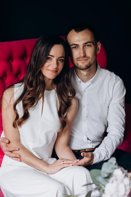 Charmant jeune couple de mariage est assis sur un canapé rose vif dans un café Photo gratuit
