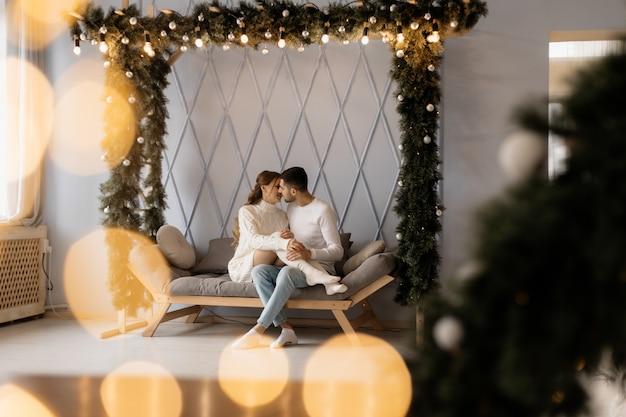 Charmant jeune couple en vêtements de maison blancs confortables pose dans une chambre avec arbre de noël Photo gratuit