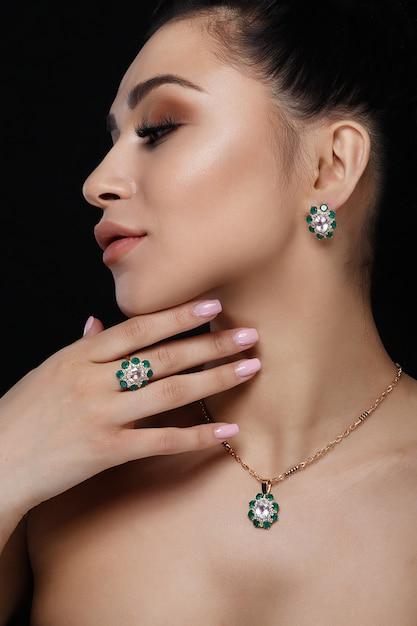Charmant modèle avec des cheveux noirs montre de riches boucles d'oreilles en or, collier et bague Photo gratuit