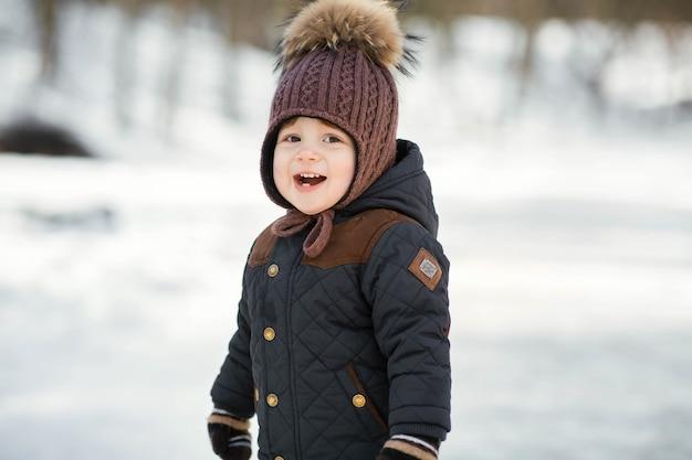 Charmant petit garçon dans un chapeau d'hiver drôle pose dans le parc Photo gratuit