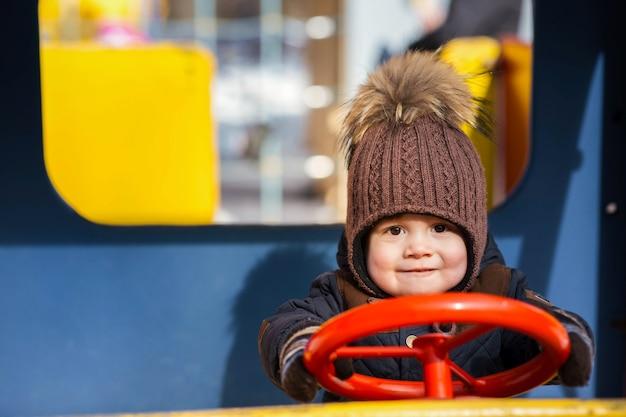Charmant petit garçon joue dans la voiture de jouet à l'extérieur Photo gratuit