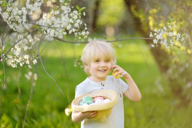 Charmant petit garçon à la recherche d'oeufs de pâques dans le parc du printemps le jour de pâques Photo Premium